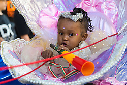 London, August 27 2017. A little girl awaits the start of the procession, her stroller decked out like a clam shell as Family Day of the Notting Hill Carnival gets underway. The Notting Hill Carnival is Europe's biggest street party held over two days of the bank holiday weekend, attracting over a million people. © Paul Davey.