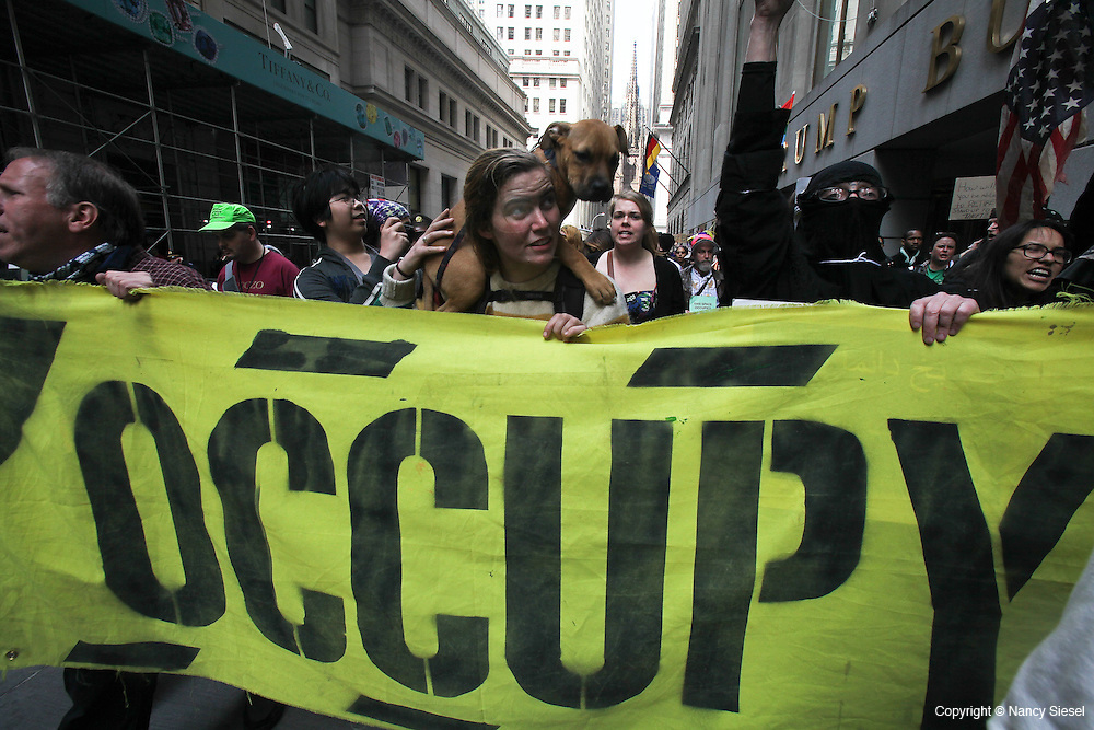 Protesters march with an Occupy banner in the financial district, on the six month anniversary of the Occupy Wall Street movement.