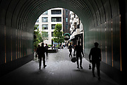 Silhouette people pass through new archway to a development called Rathbone Square off Rathbone Place in London, England, United Kingdom.