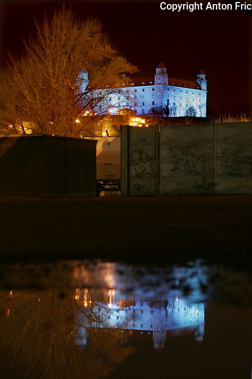 Night picture of Bratislava castle and its reflection ina puddle under the New bridge.