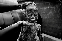 A young orphan boy is washed  before going to bed at the end of day  at the All as One orphanage in Freetown, Sierra Leone, May 2008. Photo By Andrew Parsons