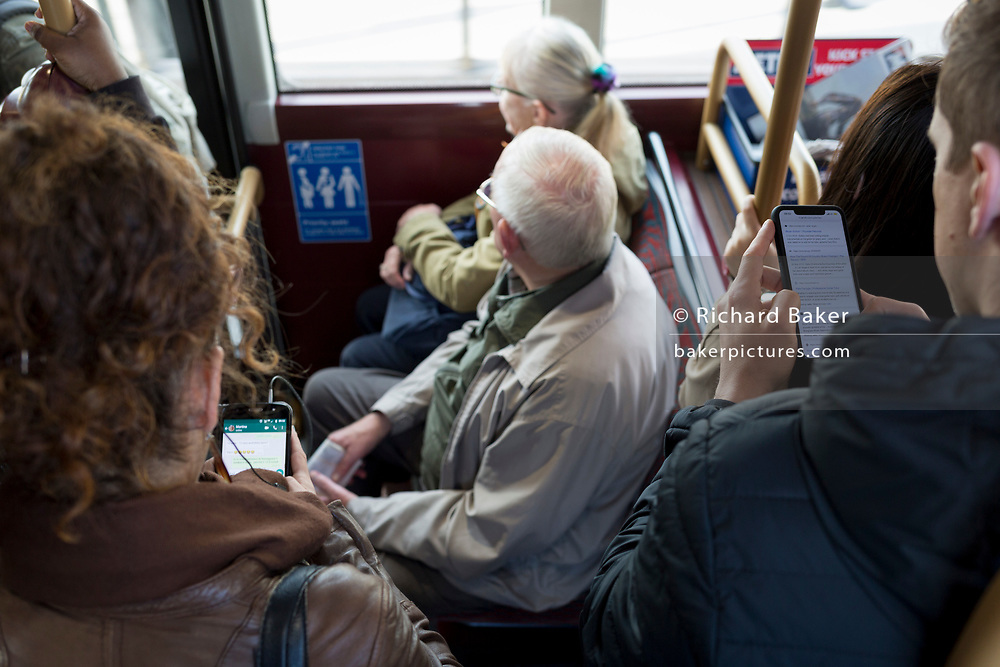 Two commuters use their phones to message whilst on board a London-bound bus during the morning rush-hour, on 9th October 2019, in London, England.