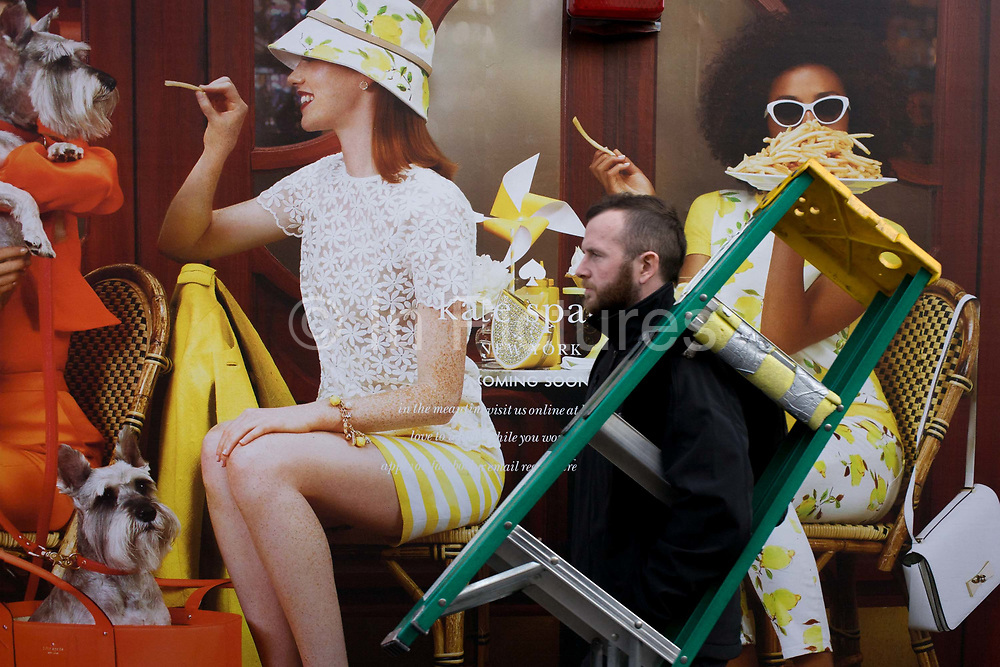 Construction hoarding for forthcoming Kate Spade in Regent Street, central London. A workman carries a small ladder on his shoulder, passing the illustration of women outside a cafe, wearing the clothing of this fashion brand. Kate Spade New York is an American fashion design house founded as Kate Spade Handbags in January 1993, by Kate Spade. The name is rendered on products (and occasionally in literature) in all lowercase (kate spade). Jack Spade is the name for the Kate Spade brand's line for men.