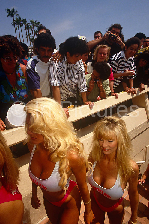 During the Cannes Film Festival, we see a group of girls from the Hawaiian Tropic company climbing some steps in bikinis and revealing apparent silicon breasts wear as a frenzy of males of various ages on La Croisette, Cannes sea front in the French Riviera resort, Cote d'Azur. They have just posed in the same corporate style for photographers along with young women publicising movies or just themselves. Hawaiian Tropic is a brand of suntan lotion who sponsor erotic bikini competitions for women who then tour the world's pageants and events like this film festival to the delight of testosterone-hungry men – young and old. Located in the Alpes-Maritimes region. Founded in 1939, the International Film Festival is one of the world's most prestigious and eccentric of celebrations of film and the cinema industry.