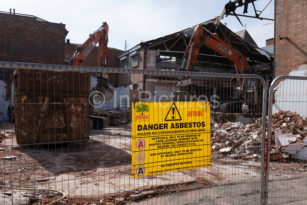 Danger Asbestos sign on a construction / demolition site on 30th March 2021 in Birmingham, United Kingdom. Asbestos is a naturally occurring fibrous mineral which is composed of long crystals, each fibre being composed of many microscopic fibrils that can be released into the atmosphere by abrasion and other processes. Asbestos is an excellent electrical insulator and is highly heat-resistant, so for many years it was used as a building material. However, it is now a well-known health and safety hazard and the use of asbestos as a building material is illegal in many countries. Inhalation of asbestos fibres can lead to various serious lung conditions, including asbestosis and cancer.