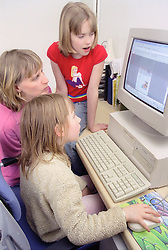 Single mother teaching young daughters to use computer,