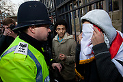 Protester refusing to show his identity is taken away by police and searched. Stop The War Coalition rally outside the US Embassy in London. Scuffles broke out during the protest, as opposite sides of the arguement shouted each other down. The protest is in response to inflamatory language being used by the US and UK concerning Iran and Syria. Free Iran supporters were came in strong numbers, to listen to speakers.