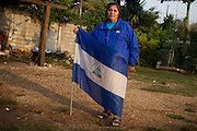 """Marta Esperanza Blandón García from Chinandega, north of Nicaragua poses for a portrait with a nicaraguan flag in Amatlán de los Reyes, Veracruz, where the caravan of central american mothers was received from """"Las Patronas"""", a local collective of women who brings free food and water to the migrants traveling in the train, on October 17th, 2012. (Photo: Prometeo Lucero)"""