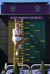 Nick McCartney from Sydney climbs the ladder at the order of play on day one of the Wimbledon Championships at the All England Lawn Tennis and Croquet Club, Wimbledon.