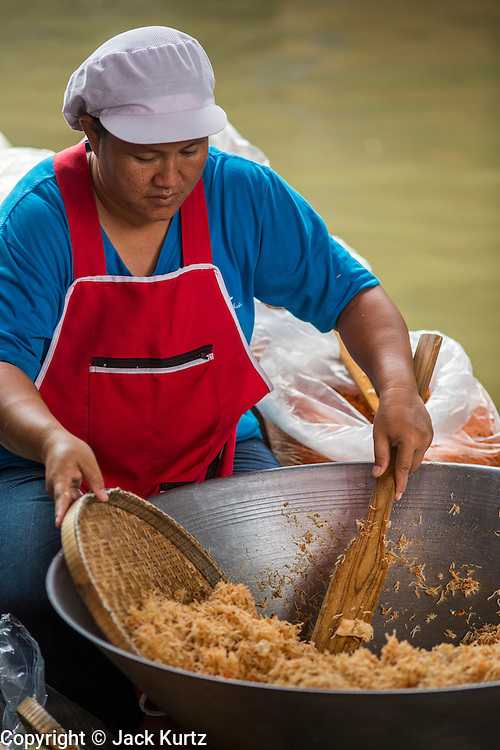 """17 NOVEMBER 2012 - BANGKOK, THAILAND:  A woman makes """"mee krob"""" (Thai fried noodles with tamarind sauce) at a floating market in the Thonburi section of Bangkok. Floating markets are common in parts of Thailand with lots of canals. Bangkok used to be known as the """"Venice of the East"""" because of the number of waterways the criss crossed the city. Now most of the waterways have been filled in but boats and ships still play an important role in daily life in Bangkok. Thousands of people commute to work daily on the Chao Phraya Express Boats and fast boats that ply Khlong Saen Saeb or use boats to get around on the canals on the Thonburi side of the river. Boats are used to haul commodities through the city to deep water ports for export.    PHOTO BY JACK KURTZ"""