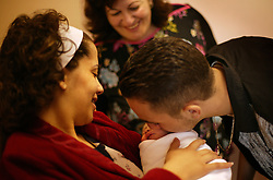 Mary Kheir is welcomed into the world by family members at Al-Dibs Maternity Hospital in Bethlehem, Palestinian Territories, Nov. 14, 2004. The baby, born into a Christian family, is the first for the Kheir family. This was the first time that the mother had held her baby.