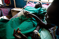 A Murle woman rests after she was operated on by Merlin staff. She was shot in the elbow as the was entering her house with her children. The police suspect she was shot by Jie trying to avenge the death of one of their tribe in Jonglei state, Southern Sudan.