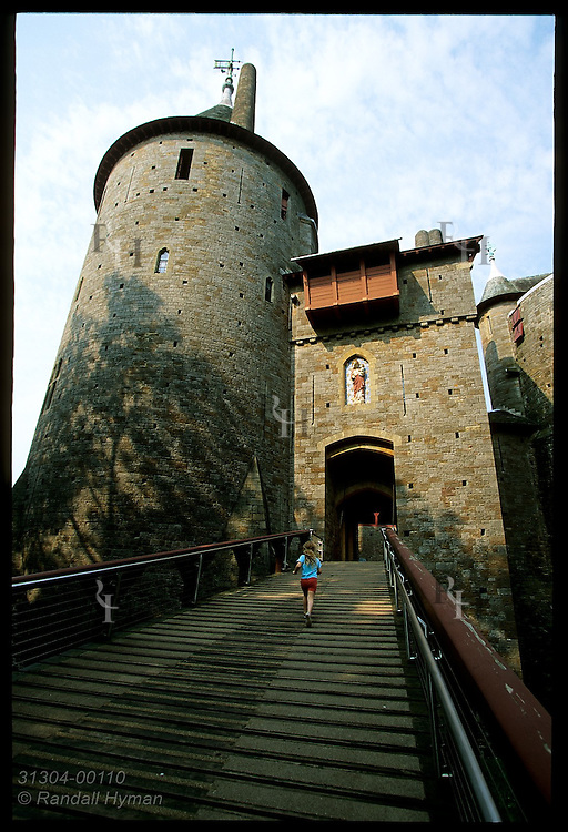 Child runs up ramp to drawbridge at Castell Coch, built 1875-91 by Wm Burges for Lord Bute on medieval ruins; Cardiff, Wales