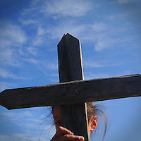 A young girl holds a wooden cross in front of a blue sky near Oaxaca, Mexico 2012
