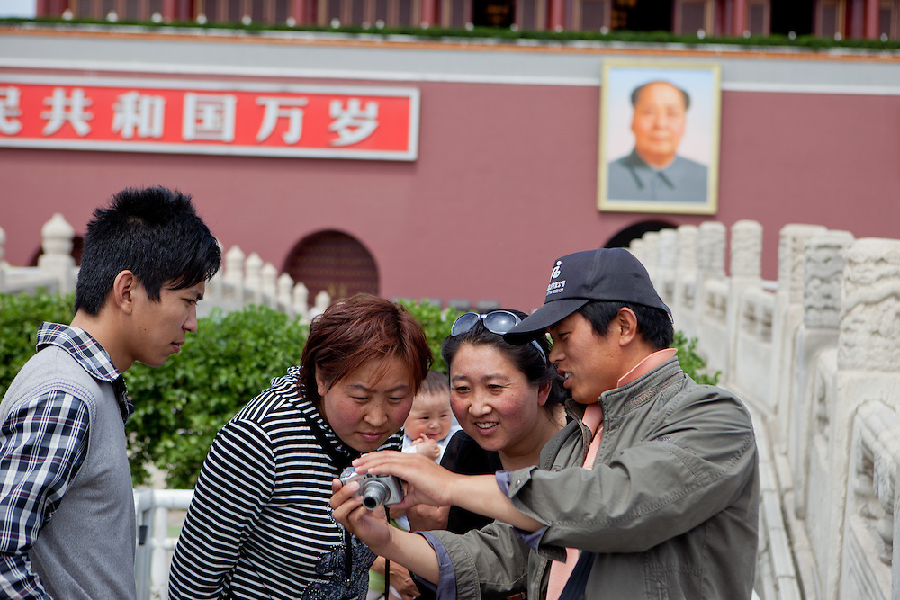 """A family is checking their digital photograph which had been made moments before at the main gate of """"The Forbidden City"""" which was the Chinese imperial palace from the Ming Dynasty to the end of the Qing Dynasty. It is located in the middle of Beijing, China. Beijing is the capital of the People's Republic of China and one of the most populous cities in the world with a population of 19,612,368 as of 2010."""