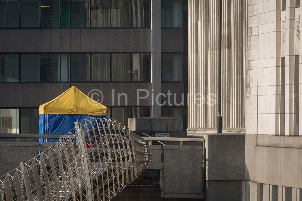 The morning after the terrorist attack at Fishmongers Hall on London Bridge, in which Usman Khan a convicted, freed terrorist killed 2 during a knife a attack, then subsequently tackled by passers-by and shot by armed police - the forensic tent where the killer was brought down is positioned near to Fishmongers Hall, on 30th November 2019, in London, England, on 30th November 2019, in London, England.