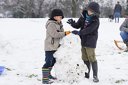 © Licensed to London News Pictures. 14/01/2021. Hexham, UK. Lucas,7, and Emily,6, try to make a snowman enjoy  the snow at Hexham Park following heavy snow last night. Photo credit: Ioannis Alexopoulos/LNP<br /> <br /> <br /> ***Permission Granted