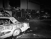 Car Bomb Damage in Dublin (E10)..1972.02.12.1972..12.02.1972..2nd December 1972..On the morning of 2nd December '72 two car bombs exploded in Dublin City. At Sackville Place two busmen were killed as they waited in their car to resume work. The busmen were named as George Bradshaw (30) and Thomas Duffy (23). The bomb was thought to be planted by a Northern Ireland subversive group who hoped to influence legislation going through Dail Eireann in relation to the I.R.A...Picture of the aftermath of the explosion at Liberty Hall, Eden Quay,Dublin. Firemen are seen hosing down the the still smouldering wreckage of several cars.