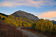 A backroad winds through beautiful aspen groves beneath stately Gothic Mountain.