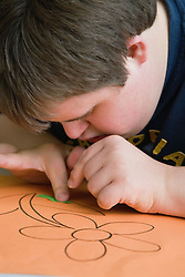 Teenage boy with Downs Syndrome drawing a picture of a flower in an art class,