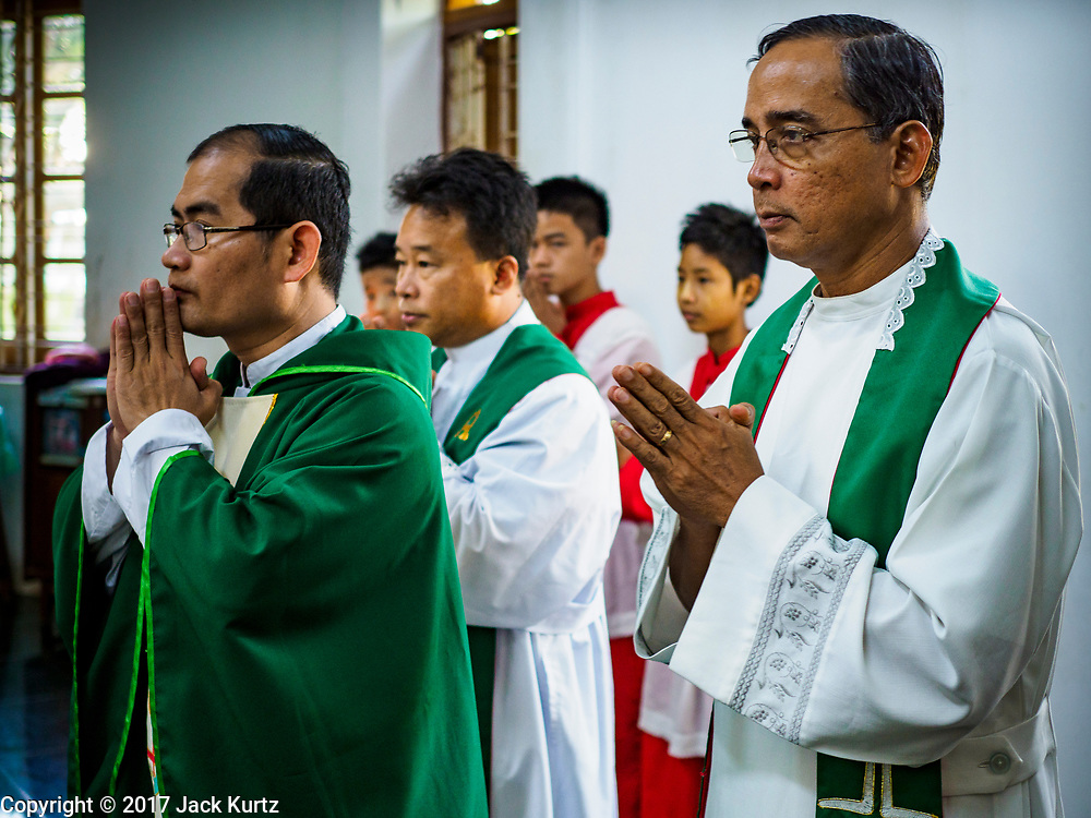 19 NOVEMBER 2017 - HWAMBI, YANGON REGION, MYANMAR: Fathers JOHN LEE (right), JEROME KYI (center) and NOEL LATT prepare to celebrate mass at Sacred Heart's Catholic Church in Hwambi, about 90 minutes north of Yangon. Catholics in Myanmar are preparing for the visit of Pope Francis. He is coming to the Buddhist majority country November 27-30. There about 500,000 Catholics in Myanmar, about 1% of the population. Catholicism was originally brought to what is now Myanmar more than 500 years ago by Portuguese missionaries and traders.    PHOTO BY JACK KURTZ