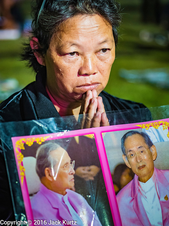 17 OCTOBER 2016 - BANGKOK, THAILAND:   A mourner with a portrait of Bhumibol Adulyadej, the late King of Thailand, gather on Sanam Luang, near the Grand Palace. Thai King Bhumibol Adulyadej died Oct. 13, 2016. He was 88. His death comes after a period of failing health. Bhumibol Adulyadej, was born in Cambridge, MA, on 5 December 1927. He was the ninth monarch of Thailand from the Chakri Dynasty and is also known as Rama IX. He became King on June 9, 1946 and served as King of Thailand for 70 years, 126 days. He was, at the time of his death, the world's longest-serving head of state and the longest-reigning monarch in Thai history.      PHOTO BY JACK KURTZ