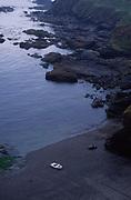 AJ02MA Small white dinghy boat alone on dark beach Lizard Point Cornwall England