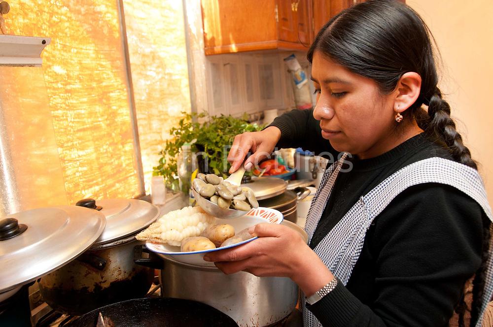 Bolivia June 2013. El Alto. Norma Barrancos, journalist, serves up lunch, a typical Bolivian dish of beans, potatoes, corn,