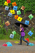 """Humorous photograph of girl with an umbrella walking through a shower of periodic elements visually depicting the saying """"Thanks for braving the elements!"""""""