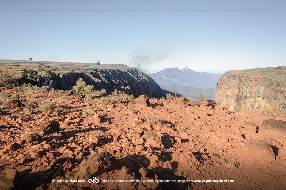 A fenda do Bimbe na Huíla ao amanhecer. Na encosta esquerda há uma queimada e fumo preto. Ao fundo vê-se o Morro Maluco. Huíla, Angola.
