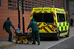 © Licensed to London News Pictures. 21/10/2021. London, UK. Hospital workers are seen pushing the stretcher outside The Royal London Hospital in east London. Health Secretary Sajid Javid warned Covid 19 cases could reach 100,000 a day this winter and urged people to take precautions against the virus. Photo credit: Marcin Nowak/LNP