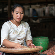 A woman uses a woven flat basket to separate the skin from small onion-like vegetables at the fish and flower market in Mandalay, Myanmar (Burma).