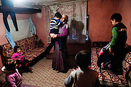 """Selcan Kesman holds her distraught son, surrounded by her children and several nieces and nephews.  Kesman shares the the tiny squatter dwelling with 3 families, 18 people in total.  Despite living in Istanbul for over ten years, the families say they are discriminated against for being Kurdish.  Feeling alone and isolated, she and her two sister-in-laws often confine themselves to the small ramshackle community they live in. The women say they feel as though integration is much harder for them than their husbands. """"We can't even ask our neighbors to watch our kids,"""" said her sister in-law, Gulcan Kesman.<br /> (photo by Amanda Voisard)"""