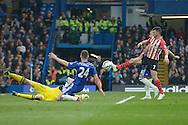 Shane Long of Southampton attempts to punt the ball past Goalkeeper Thibaut Courtois of Chelsea and Gary Cahill of Chelsea. Barclays Premier league match, Chelsea v Southampton at Stamford Bridge in London on Sunday 15th March 2015.<br /> pic by John Patrick Fletcher, Andrew Orchard sports photography.