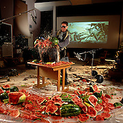 """A sound engineer bashes watermelons on a foley sound stage at Sony Studios to mimick insects biting through humans for a fight scene in the science fiction thriller """"Stormship Troopers"""" on the screen  behind him."""