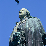 A bird flying over a statue of George Washington outside the Pike Place Market in Seattle, Washington