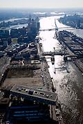 Nederland, Zuid-Holland, Rotterdam, 20-03-2009; onder in beeld de Nassaukade in de wijk Feijenoord, gebouw de Brug, hoofdkantoor van Unilever Nederland B.V, gebouwd boven een oude margarinefabriek. In het kantoorgebouw De Brug ook dochteronderneming Unilever Foodsolutions (voert o.a. de merknamen Knorr, Unox, Calvé, Becel en Conimex). Op de verschillende braakliggende en leegstaande terreinen zullen stadswoningen gebouwd worden. Geheel rechts het Noordereiland met 'De Hef', voormalige spoorburg (vakwerkbrug) en daarachter de Koninginnebrug. Erasmusbrug en Kop van Zuid in de verte. Air view on  the river Meuse of Rotterdam. The head office of Unilever is called Building The Bridge, on the south bank (r), the isle of North (m)  and the bridges the Hef (Lift), a lattice bridge connecting the south bank and the isle and the Erasmusbrug, connecting the South and North bank ..Swart collectie, luchtfoto (toeslag); Swart Collection, aerial photo (additional fee required).foto Siebe Swart / photo Siebe Swart