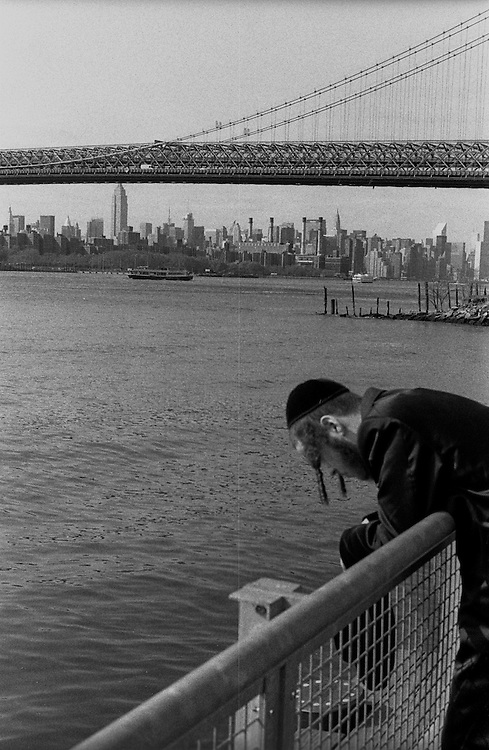 """Orthodox Jews looking back at Manhattan on the East River in the Williamsburg neighborhood of Brooklyn...Part of long-term (2005-2008) story """"I See A Darkness"""". New York, NY."""