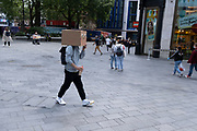 A man walks through Leicester Square with a cardboard box on his head, on 23rd June 2021, in Westminster, London, England.