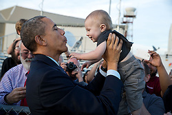 President Barack Obama holds a child while greeting people on the tarmac upon arrival at San Francisco International Airport in San Francisco, Calif., Feb. 12, 2015. (Official White House Photo by Pete Souza)<br /> <br /> This official White House photograph is being made available only for publication by news organizations and/or for personal use printing by the subject(s) of the photograph. The photograph may not be manipulated in any way and may not be used in commercial or political materials, advertisements, emails, products, promotions that in any way suggests approval or endorsement of the President, the First Family, or the White House.