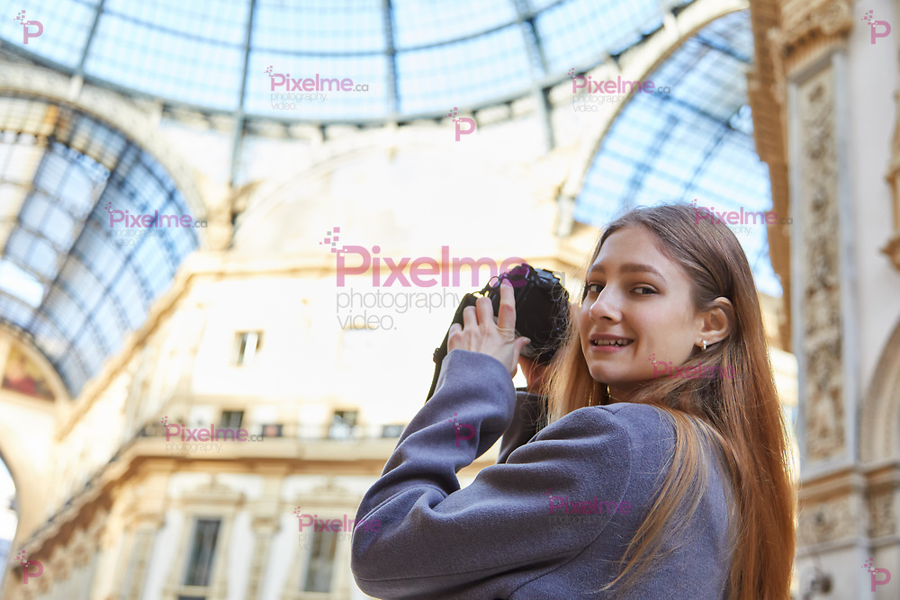 Tourist girl smile and takes a photo in Galleria Vittorio Emanuele II during the day in Milan Italy