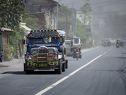 January 30, 2018 - Guinobatan, Albay, Philippines - Traffic in Guinobatan during an ash fall caused by Mayon volcano. The volcano continued to erupt but not as dramatically as it did last week. The small eruptions are still sending ash clouds over communities west of the volcano and the government is encouraging people to stay indoors, wear face masks and avoid strenuous activities when ash is falling. (Credit Image: © Jack Kurtz via ZUMA Wire)