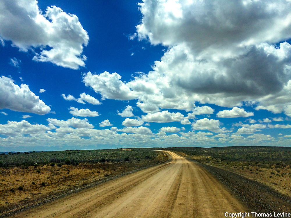 The dirt road to Chaco Canyon in New Mexico.  During rainy weather a 4-wheel drive vehicle is a must. This was a sunny day with low broken clouds and blue sky. iPhone