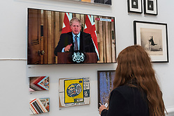 """© Licensed to London News Pictures. 28/09/2020. LONDON, UK. A staff member views a digital video of Boris Johnson addressing the nation, """"Twice"""" by John SMith.  Preview of the Summer Exhibition at the Royal Academy of Arts in Piccadilly which, due to the Covid-19 lockdown, is taking place for the first time in the autumn.  Over 1000 works in a range of media by Royal Academicians, established and emerging artists, feature in the exhibition which runs from 6 October 2020 – 3 January 2021.  Photo credit: Stephen Chung/LNP"""