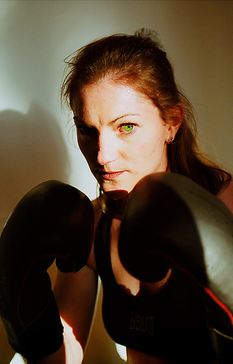 Female boxer in fighter in fighting stances .