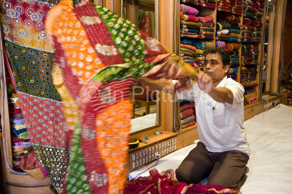 A man selling material in the Johari Bazaar, Jaipur, India