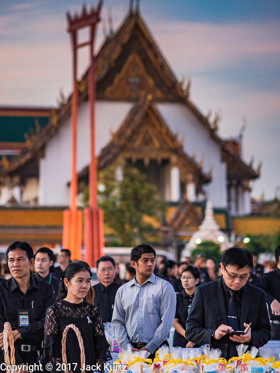 20 JANUARY 2017 - BANGKOK, THAILAND: People wait for a Buddhist religious ceremony to start on the plaza between Wat Suthat (in the background) and Bangkok's City Hall. Hundreds of municipal workers and civil servants made merit by praying and presenting alms to 89 Buddhist monks Friday to mark 100 days of mourning since the death of revered Bhumibol Adulyadej, the Late King of Thailand. The significance of 89 monks is that the King, who died on October 13, 2016, was a few weeks short of his 89th birthday.       PHOTO BY JACK KURTZ