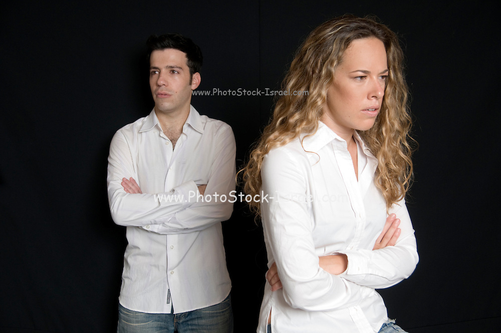 An angry young couple in their 20s on a black background Model Releases available