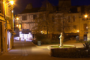 The old stone statue of Cyrano de Bergerac on Place Pelissiere Square in Bergerac. At night with houses lit up on the town square. Bergerac Dordogne France