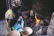 Fatoumata breast-feeds her child while cooking dinner on a wood fire at her co-wife's home compound, Kouakourou, Mali. The Natomo family lives in two mud brick houses in the village of Kouakourou, Mali, on the banks of the Niger River. They are grain traders and own a mango orchard. According to tradition Soumana is allowed to take up to four wives; he has two. Wives Pama and Fatoumata are partners in the family and care for their many children together. Material World Project.
